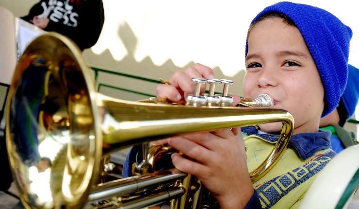 menino com camiseta amarela e touca azul está tocando um trompete