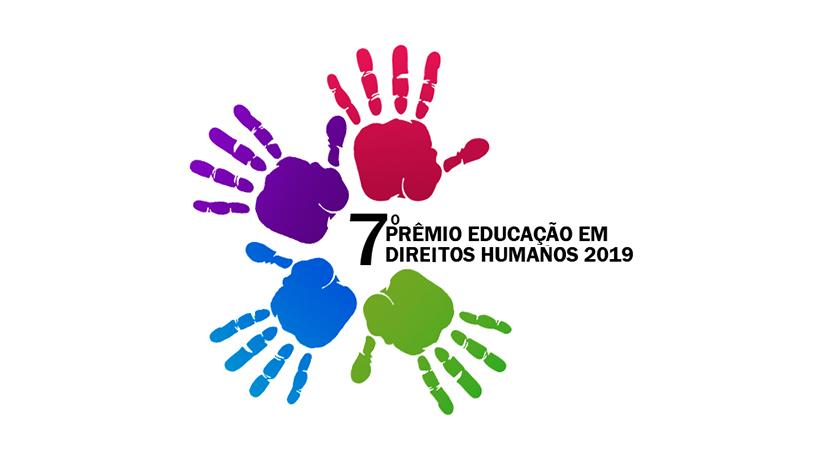 Imagem com fundo branco apresenta no centro, o logotipo do 7º Prêmio Educação em Direitos Humanos 2019 representado quatro mãos de diferentes cores.