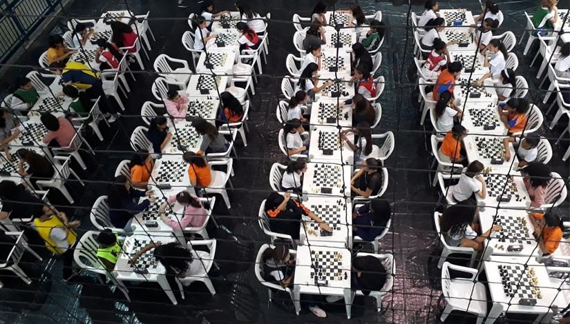 Imagem de cima da Final Regional de Xadrez individual, mostrando as mesas com as crianças sentadas.