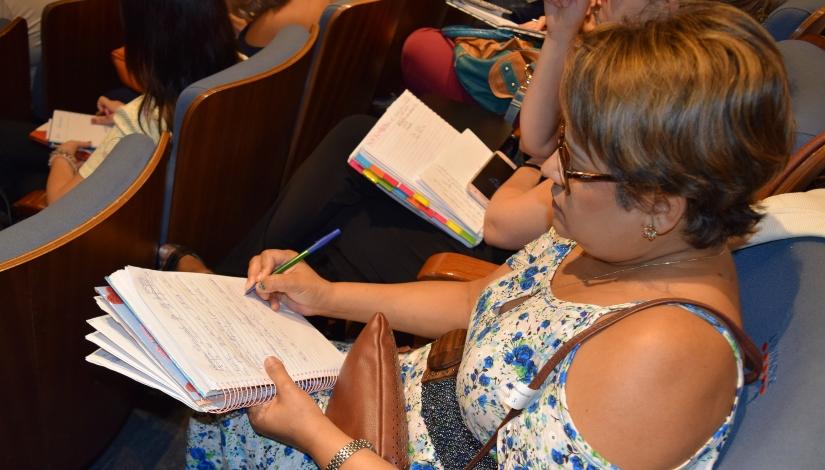 A fotografia mostra uma educadora da Rede Municipal de Ensino sentada segurando um caderno e fazendo anotações.