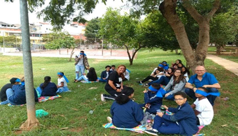 Grupo de alunos sentados na grama ao lado de uma arvore.