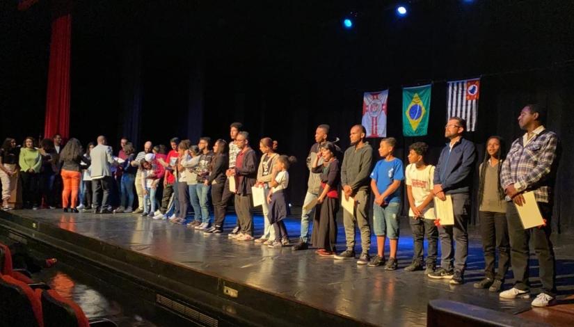 Imagem mostra estudantes e educadores no palco do auditório do CEU Alvarenga recebendo certificados.
