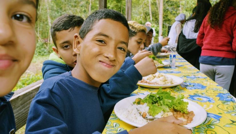 Imagem mostra aproximadamente cinco estudantes sentados na mesma mesa, um ao lado da outro se alimentado, um deles, um menino, está posando para foto e comendo.