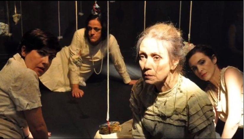Quatro mulheres sentadas no chão com cenário de cordas penduradas -cena da peça mulheres insubmissas