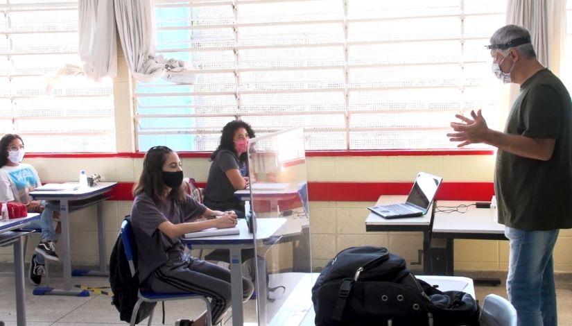Foto de um professor com equipamentos de proteção individual e estudantes usando máscaras sentas às suas carteiras na sala de aula