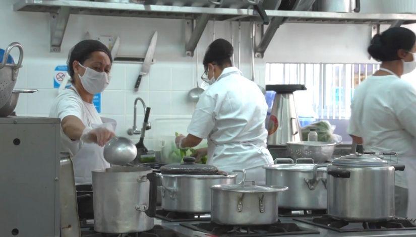 três cozinheiras trabalhando em cozinha escolar. todas utilizam máscara