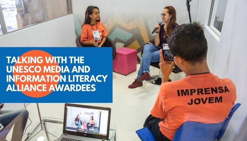 Fotografia de estudantes do Projeto Imprensa Jovem entrevistando uma pessoa em um estúdio. Imagem segue com banner do evento da unesco