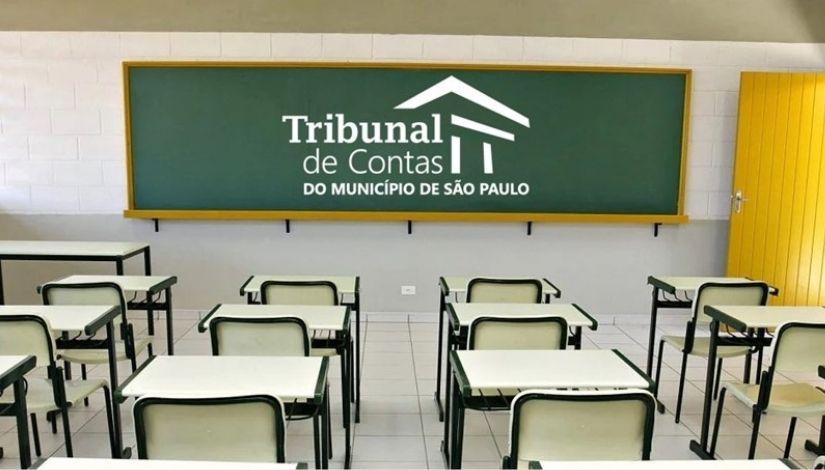 Imagem mostra uma sala de aula com as mesas e cadeiras vazias, na lousa a logomarca escrito: Tribunal de Contas do Município de São Paulo.