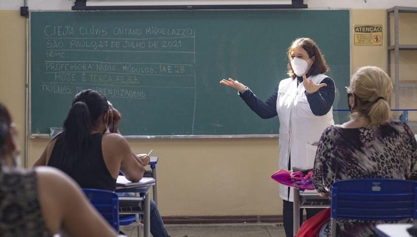 Fotografia de uma professora em momento de aula com estudantes que estão sentadas em suas cadeias. Ao fundo, tem uma lousa verde onde se-lê