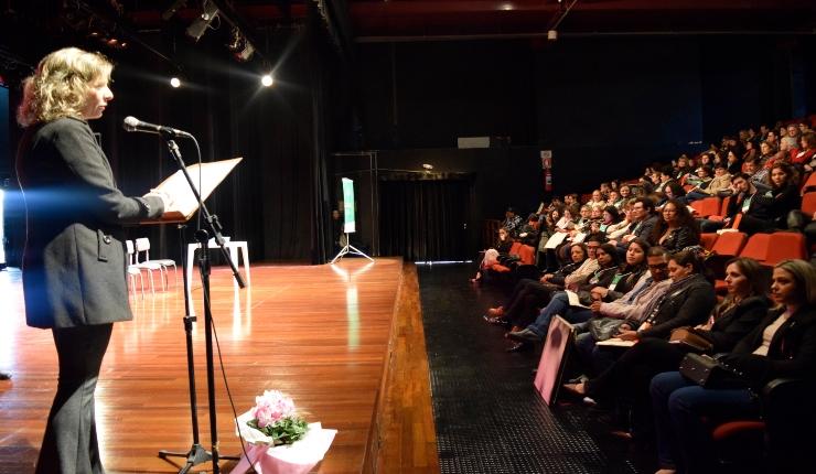 no lado esquerdo da foto no palco uma mulher loira com roupa preta, falando ao microfone. No lado direito da imagem, publico do auditório.